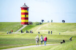 Tourists walk on the dike in front of the Pilsum lighthouse in the municipality of Krummhoern, Germany, Thursday, may 28, 2020. The lighthouse with its red-yellow striped painting served as a backdrop for several feature films. Since 2004 it is also used for civil weddings. (Hauke-Christian Dittrich/dpa via AP)