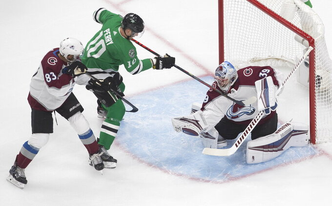 Dallas Stars' Corey Perry (10) tries to get the puck loose from Colorado Avalanche goalie Pavel Francouz (39) as Avalanche's Matt Nieto (83) defends during first period NHL qualifying round game action in Edmonton, on Wednesday, Aug. 5, 2020. (Jason Franson/The Canadian Press via AP)