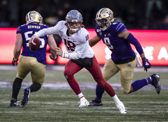 Washington State quarterback Anthony Gordon scrambles out of the pocket as he is chased by Washington linebacker Joe Tryon during the second half of an NCAA college football game, on Friday, Nov. 29, 2019 in Seattle. Washington won 31-13. (AP Photo/Stephen Brashear)