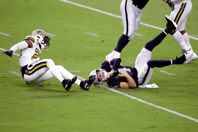 New Orleans Saints strong safety Malcolm Jenkins, left, sacks Las Vegas Raiders quarterback Derek Carr (4) during the first half of an NFL football game, Monday, Sept. 21, 2020, in Las Vegas. (AP Photo/Isaac Brekken)