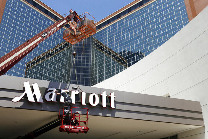 FILE - In this Tuesday, April 30, 2013, file photo, a man works on a new Marriott sign in front of the former Peabody Hotel in Little Rock, Ark.  Marriott says the information of up to 500 million guests at its Starwood hotels has been compromised. It said Friday, Nov. 30, 2018,  that there was a breach of its database in September, but also found out through an investigation that there has been unauthorized access to the Starwood network since 2014. (AP Photo/Danny Johnston, File)