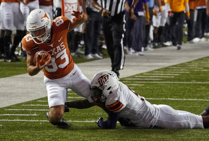Texas's Kai Money (83) is tackled by UTEP's Dy'Vonne Inyang (5) during the first half of an NCAA college football game in Austin, Texas, Saturday, Sept. 12, 2020. (AP Photo/Chuck Burton)