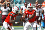 Miami quarterback Jarren Williams (15) hands off to running back DeeJay Dallas (13) during the first half of an NCAA college football game against Bethune-Cookman, Saturday, Sept. 14, 2019, in Miami Gardens, Fla. (AP Photo/Wilfredo Lee)
