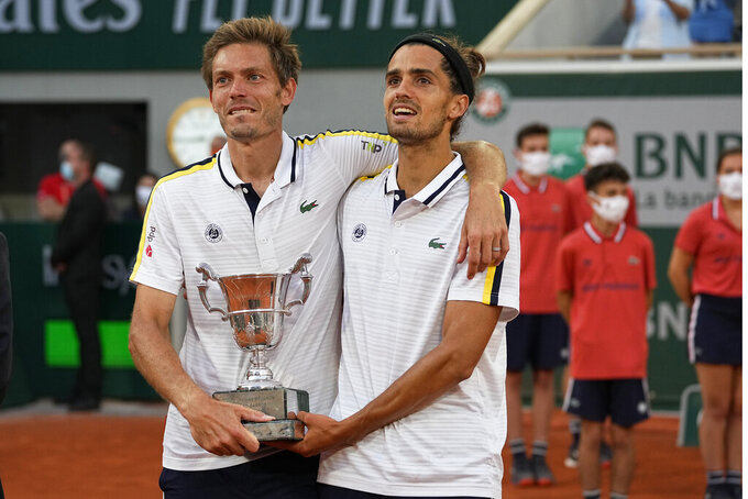 France's Nicolas Mahut, left, and Pierre-Hugues Herbert hold tier trophy after defeating Kazakstan's Alexander Bublik and Andrey Golubev in their men's doubles final match of the French Open tennis tournament at the Roland Garros stadium Saturday, June 12, 2021 in Paris. (AP Photo/Michel Euler)