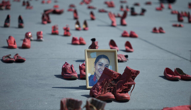 A portrait of Eugenia Machuca Campos sits amid women's red shoes placed by activists to protest violence against women in the Zocalo, Mexico City's main plaza, Saturday, Jan. 11, 2020. According to her sister, Campos' ex-boyfriend is serving time in jail for her Oct. 2017 murder in the State of Mexico. (AP Photo/Christian Palma)
