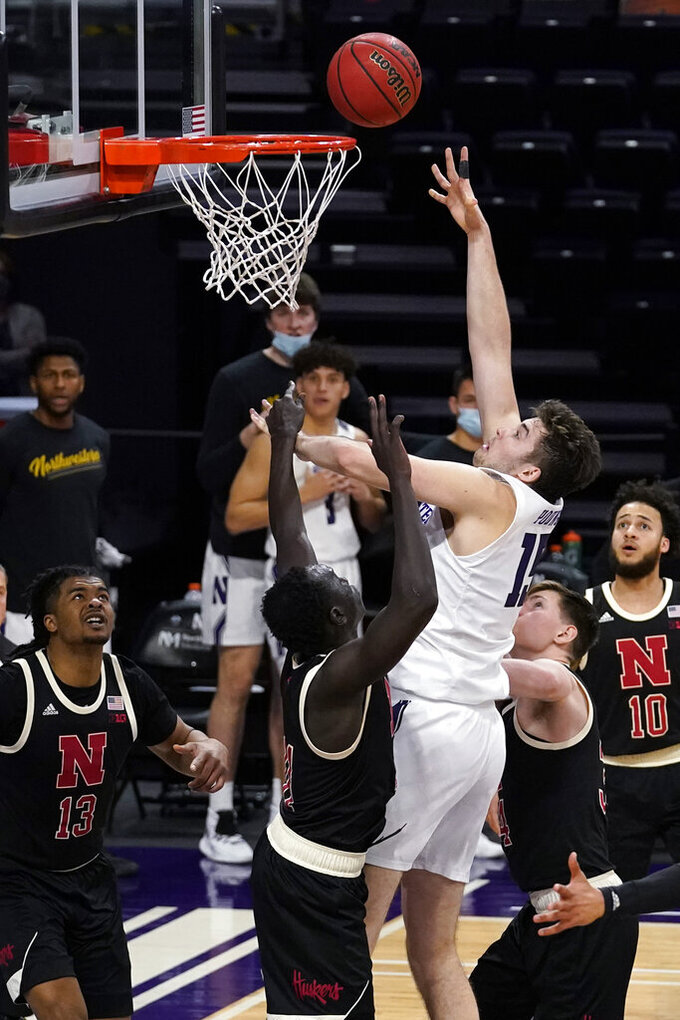Northwestern center Ryan Young, center, shoots against Nebraska forward Lat Mayen and guard Thorir Thorbjarnarson during the second half of an NCAA college basketball game in Evanston, Ill., Sunday, March 7, 2021.  (AP Photo/Nam Y. Huh)