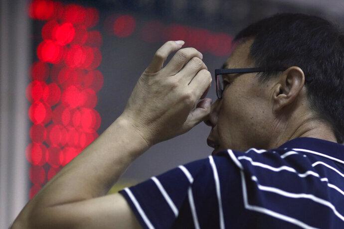 In this Sept. 25, 2019, photo, a Chinese man adjusts his glasses as he monitors stock prices at a brokerage in Beijing. Asian stock markets followed Wall Street higher Thursday, Sept. 26, 2019, after U.S. President Donald Trump suggested a costly tariff war with China could be resolved soon. (AP Photo/Ng Han Guan)