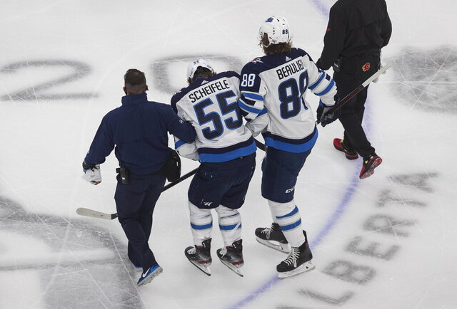 Winnipeg Jets' Mark Scheifele is helped off the ice after being injured during the first period of the team's NHL hockey playoff game against the Calgary Flames in Edmonton, Alberta, Saturday, Aug. 1, 2020. (Jason Franson/The Canadian Press via AP)