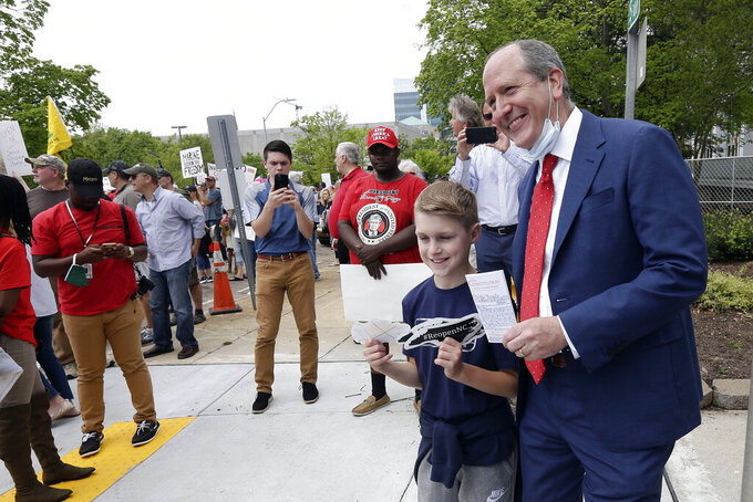 In this April 21, 2020, photo, Rep. Dan Bishop, R-N.C., right, has a photo taken with a youngster during a ReopenNC demonstration in Raleigh, N.C., urging Gov. Roy Cooper to allow businesses to reopen during the coronavirus outbreak. (AP Photo/Gerry Broome)