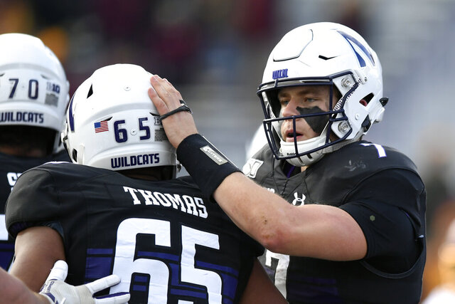 Northwestern quarterback Andrew Marty (7) celebrates with teammate Jared Thomas (65) after rushing for a touchdown during the second half of an NCAA football game against Minnesota Saturday, Nov. 23, 2019, in Evanston, Ill. Minnesota won 38-22. (AP Photo/Paul Beaty)