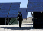 FILE - In this Friday, April 3, 2015 file photo, President Barack Obama walks through a solar array at Hill Air Force Base, Utah to speak about clean energy and the jobs numbers. Driven by concerns about rising global greenhouse gas emissions, President Donald Trump's rollback of the Obama administration's Clean Power Plan and his plans to pull the United States out of the 2015 Paris climate agreement, some states are turning to renewable energy targets and energy efficiency programs in hopes of addressing climate change. (AP Photo/Carolyn Kaster)
