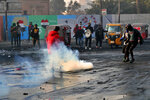 Protesters grab tear gas canisters during ongoing protests in central Baghdad, Iraq, Monday, Jan. 20, 2020. (AP Photo/Khalid Mohammed)