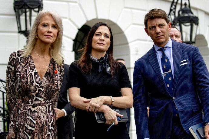 From left, counselor to the President Kellyanne Conway, White House press secretary Stephanie Grisham, and Deputy White House press secretary Hogan Gidley, listen as President Donald Trump speaks to the media on the South Lawn of the White House in Washington, Thursday, Oct. 3, 2019, before boarding Marine One for a short trip to Andrews Air Force Base, Md., and then on to Florida. (AP Photo/Andrew Harnik)