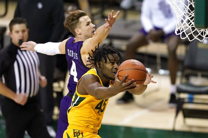 Baylor guard Davion Mitchell (45) goes up for a shot as Stephen F. Austin's David Kachelries (4) defends during the first half of an NCAA college basketball game in Waco, Texas, Wednesday, Dec. 9, 2020. (AP Photo/Tony Gutierrez)
