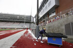 FILE - In this Dec. 12, 2020, file photo, California student equipment manager Will O'Connor removes equipment from Martin Stadium in Pullman, Wash., after the NCAA college football game between Washington State and California was canceled because of a case of COVID-19 on the Cal team. More than 130 games were canceled or postponed in major college football last season, even though most schools played truncated or conference-only schedules. (AP Photo/Young Kwak, File)