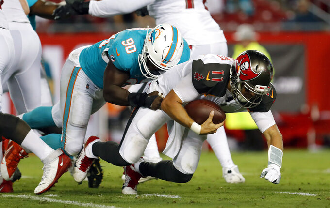 Miami Dolphins defensive end Charles Harris (90) sacks Tampa Bay Buccaneers quarterback Blaine Gabbert (11) during the first half of an NFL preseason football game Friday, Aug. 16, 2019, in Tampa, Fla. (AP Photo/Mark LoMoglio)