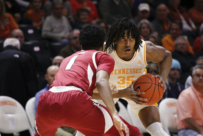 Tennessee forward Yves Pons (35) looks for an open man while Arkansas guard Isaiah Joe (1) defends in the first half of an NCAA college basketball game, Tuesday, Jan. 15, 2019, in Knoxville, Tenn. (AP Photo/Shawn Millsaps)