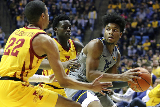 West Virginia guard Miles McBride (4) goes to pass the ball as he is defended by Iowa State guards Tyrese Haliburton (22) and Terrence Lewis (24) during the first half of an NCAA college basketball game Wednesday, Feb. 5, 2020, in Morgantown, W.Va. (AP Photo/Kathleen Batten)
