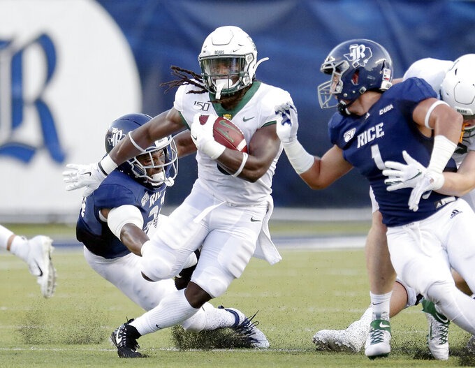 Baylor running back JaMycal Hasty, middle, makes a gain between Rice defensive end Anthony Ekpe, left, and linebacker Antonio Montero (1) during the first half of an NCAA college football game Saturday, Sept. 21, 2019, in Houston. (AP Photo/Michael Wyke)