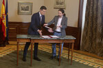 Spain's caretaker Prime Minister Pedro Sanchez, left, and Podemos party leader Pablo Iglesias exchange documents while signing an agreement at the parliament in Madrid, Spain, Tuesday, Nov. 12, 2019. The leaders of Spain's Socialist party and the left-wing United We Can (Podemos) party say they have reached a preliminary agreement toward forming a coalition government. But the deal announced Tuesday won't provide enough votes in parliament for the Socialists, who won a general election, to take office without the support of other parties. (AP Photo/Paul White)