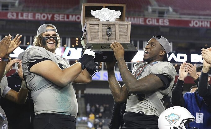 Central Florida's Jake Brown, left, and Nate Evans hoist the trophy after the team's win over Marshall during the Gasparilla Bowl NCAA college football game Monday, Dec. 23, 2019, in Tampa, Fla. (Stephen M. Dowell/Orlando Sentinel via AP)