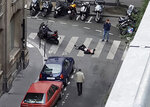 An unidentified man covered in blood lays on a street in Paris Saturday May 12, 2018, as two people look at him. The image was taken by a bystander who filmed the aftermath of a knife attack in Paris in which a 29-year-old man was stabbed to death and four others injured on Saturday evening. The Paris police said the attacker was subdued by officers during the stabbing attack in the 2nd arrondissement or district of the French capital.(Wladia Drummond via AP)