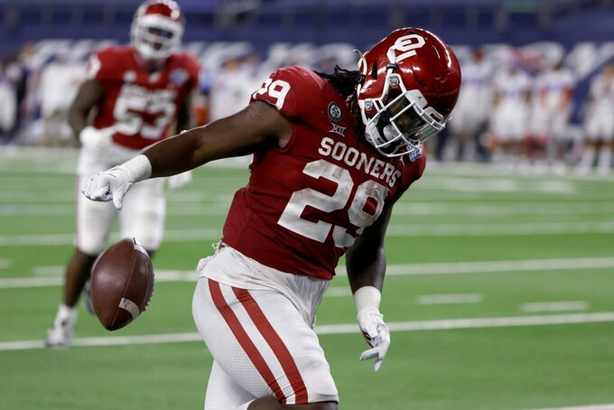Oklahoma running back Rhamondre Stevenson releases the ball after reaching the end zone for a touchdown in the second half of the team's Cotton Bowl NCAA college football game against Florida in Arlington, Texas, Wednesday, Dec. 30, 2020. (AP Photo/Ron Jenkins)