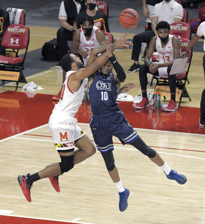 Maryland forward Galin Smith,left, collides with Old Dominion guard Xavier Green (10) as he leaps for a pass during the first half of an NCAA college basketball game in College Park, Md., Wednesday, Nov. 25, 2020. (Karl Merton Ferron/The Baltimore Sun via AP)