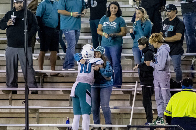 Coastal Carolina quarterback Grayson McCall (10) goes into the stands to give a fan a hug following a win over Troy at an NCAA college football game, Saturday, Dec. 12, 2020, in Troy, Ala. (AP Photo/Vasha Hunt)