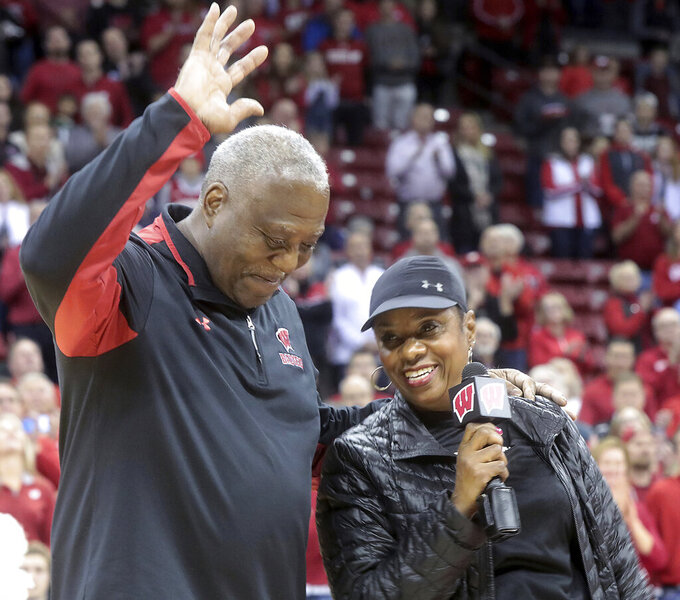 Howard Moore Sr. and his wife, Trennis, acknowledge the crowd after a tribute to their son, Wisconsin assistant coach Howard Moore, before the team's NCAA college basketball game against Eastern Illinois in Madison, Wis., Friday, Nov. 8, 2019. Moore was involved in May 25 vehicle crash that claimed the life of his wife, Jennifer, and daughter, Jaidyn. He has continued to face health challenges since the accident was unable to attend the game. (John Hart/Wisconsin State Journal via AP)