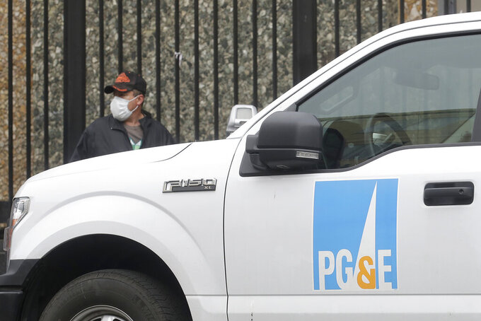 FILE - In this April 16, 2020, file photo, a man wearing a mask walks behind a Pacific Gas and Electric truck in San Francisco. California power regulators are poised to reprimand Pacific Gas and Electric for continuing to neglect its electrical grid that has ignited a series of deadly wildfires in Northern California and could order the utility to do be more vigilant in the upcoming months of hot, windy weather. The anticipated rebuke from the California Public Utilities Commission Thursday, April 15, 2021, would serve as official notice to PG&E that it hasn't been doing enough to reduce the risks posed by a combination of crumbling equipment and overgrown trees susceptible to touching or toppling into nearby power lines. (AP Photo/Jeff Chiu, File)