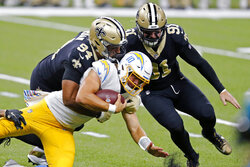 Los Angeles Chargers quarterback Justin Herbert (10) carries as he is tackled by New Orleans Saints defensive end Cameron Jordan (94) and defensive end Trey Hendrickson (91) in the first half of an NFL football game in New Orleans, Monday, Oct. 12, 2020. (AP Photo/Brett Duke)