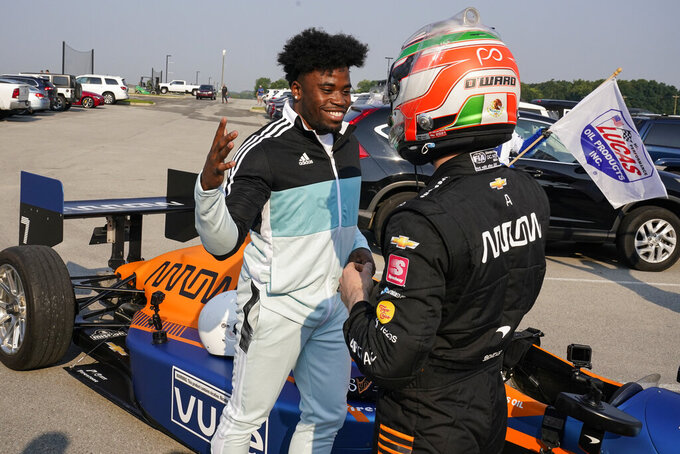Indianapolis Colts cornerback Kenny Moore II, left, thanks IndyCar driver Pato O'Ward for a ride into the Colts training camp in the back seat of a two-seat IndyCar as the players reported to the NFL team's football training camp in Westfield, Ind., Tuesday, July 27, 2021. Practice open on Wednesday. (AP Photo/Michael Conroy)