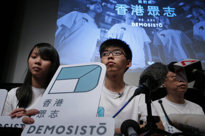In this April 10, 2016, photo, Hong Kong teen activist Joshua Wong, center, and members of their new political party Demosisto listen to a reporter's questions as they officially unveiled during a press conference in Hong Kong. After a security law for Hong Kong passed in China, prominent Hong Kong pro-democracy activists Wong, Agnes Chow and Nathan Law issued statements on Facebook on Tuesday, June 30, 2020, saying they would withdraw from the pro-democracy organization Demosisto. Wong said