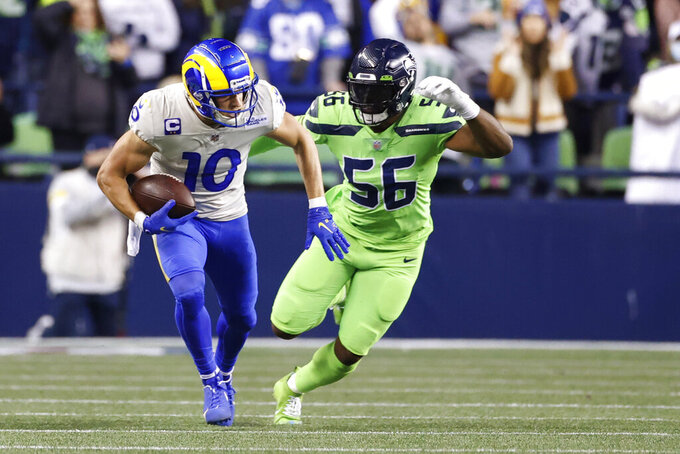 Los Angeles Rams wide receiver Cooper Kupp (10) moves to avoid Seattle Seahawks linebacker Jordyn Brooks (56) during the second half of an NFL football game, Thursday, Oct. 7, 2021, in Seattle. The Rams won 26-17. (AP Photo/Craig Mitchelldyer)