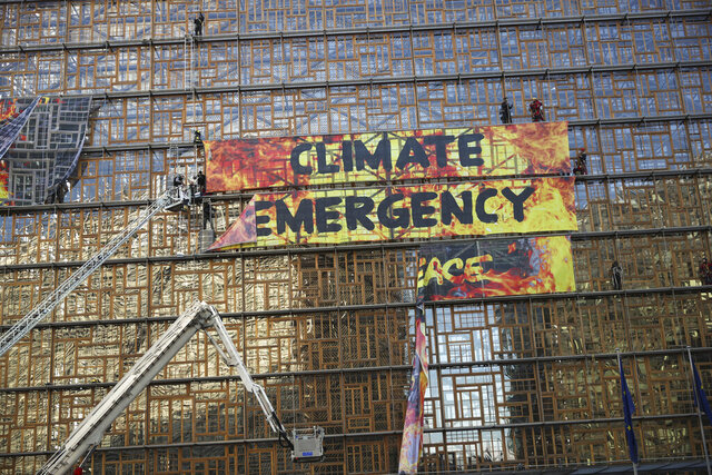 Police and fire personnel move in to remove climate activists after they climbed the Europa building during a demonstration outside an EU summit meeting in Brussels, Thursday, Dec. 12, 2019. Greenpeace activists on Thursday scaled the European Union's new headquarters, unfurling a huge banner warning of a climate emergency hours before the bloc's leaders gather for a summit focused on plans to combat global warming.(AP Photo/Francisco Seco)