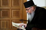 A priest reads a book at the Archbishopric in Nicosia, Cyprus on Friday, Sept. 6, 2019. Cyprus' Archbishop Chrysostomos says he will ask the Russian Orthodox Patriarch to act so that a Russian priest stops conducting liturgical services at a pair of churches in the breakaway Turkish Cypriot north of the ethnically divided island nation. (AP Photo/Petros Karadjias)