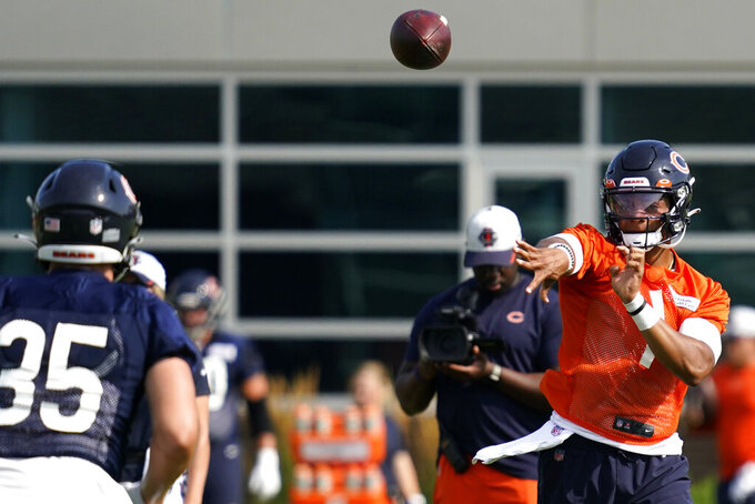 Chicago Bears quarterback Justin Fields, right, works with running back Ryan Nall (35) during NFL football practice in Lake Forest, Ill., Saturday, July 31, 2021. (AP Photo/Nam Y. Huh)