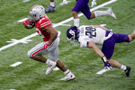 Ohio State running back Master Teague III, left, runs with the ball past Northwestern linebacker Chris Bergin (28) during the first half of the Big Ten championship NCAA college football game, Saturday, Dec. 19, 2020, in Indianapolis. (AP Photo/Darron Cummings)