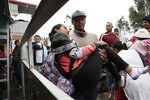 A woman who collapsed is carried by her husband, on the Rumichaca bridge, before crossing the border from Colombia to Ecuador, Thursday, June 13, 2019. Venezuelan migrants are making their way to Peru, where on June 15, the country will start requiring them to have a passport and a humanitarian visa. (AP Photo/Dolores Ochoa)