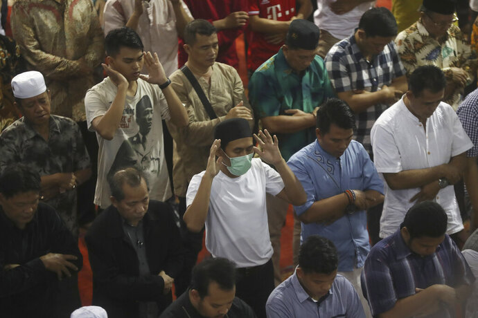 In this Feb. 14, 2020, photo, a man wear mask during Friday prays at the Istiqlal Mosque in Jakarta, Indonesia. Indonesia, the world's largest Muslim-majority country, has not had a case of infection of a deadly viral outbreak that started in China and residents walk about and pray in groups five times a day in mosques without masks. The outbreak has infected more than ten of thousands of people worldwide and killed more than 1,000 where the new coronavirus strain was first detected in December. (AP Photo/Achmad Ibrahim)
