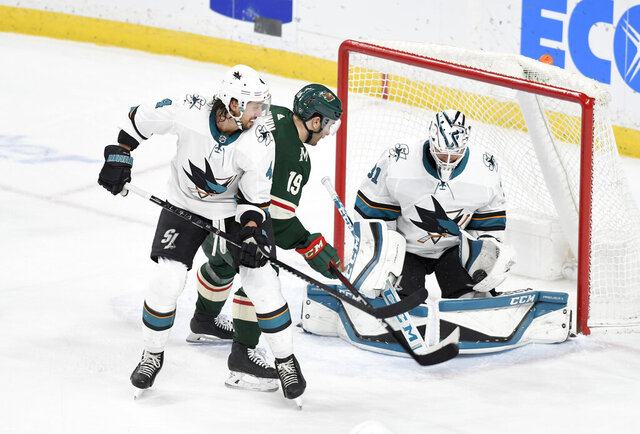 San Jose Sharks' goalie Martin Jones, right, makes a glove save on a shot by Minnesota Wild's Jason Zucker (16) behind the Sharks' Brenden Dillon in the third period of an NHL hockey game, Saturday, Feb. 15, 2020, in St. Paul, Minn. San Jose won 2-0.(AP Photo/Tom Olmscheid)