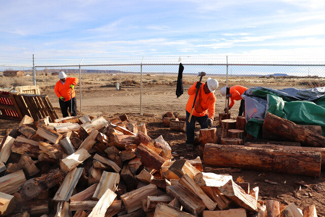 In this Dec. 6, 2019, photo, workers employed by the Village of Tewa chop wood delivered from the White Mountain Apache Timber Company in the Village of the Tewa administration building on the Hopi Nation, in Ariz. Navajo and Hopi families in northeastern Arizona that have long relied on coal to heat their homes are looking to other sources after last year's closure of a coal mine. (Melissa L. Sevigny/Arizona Public Radio via AP)