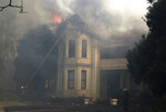 Firefighters douse a burning building at the University of Cape Town, South Africa, Sunday, April 18, 2021. A wildfire raging on the slopes of Table Mountain forced students to evacuate their residence as firefighters battled the blaze. (AP Photo/Nardus Engelbrecht)