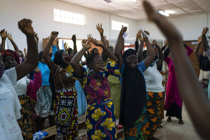 Pregnant women sing and dance before being assisted in a health unit where several women look for assistance with prenatal care in Koidu, district of Kono, Sierra Leone, Tuesday, Nov. 24, 2020. (AP Photo/Leo Correa)
