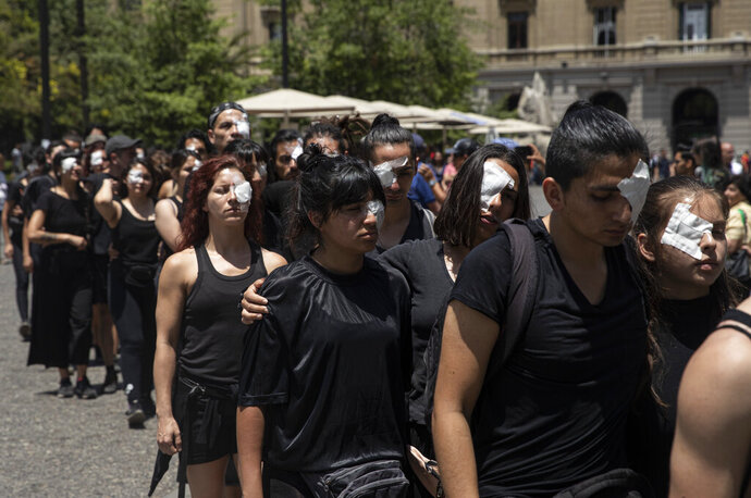 Anti-government demonstrators, wearing eye patches, perform in front of the Supreme Court in Santiago, Chile, Monday, Nov. 18, 2019. According to the Medical College of Chile at least 230 people have lost sight after being shot in an eye in the last month while participating in the demonstrations over inequality and better social services. (AP Photo/Esteban Felix)