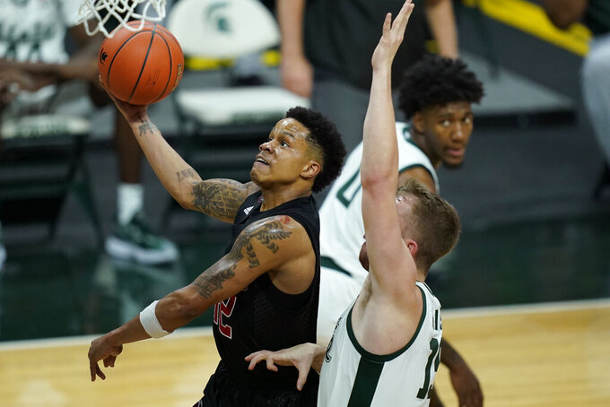 Rutgers guard Jacob Young (42) makes a layup as Michigan State forward Thomas Kithier (15) defends during the first half of an NCAA college basketball game, Tuesday, Jan. 5, 2021, in East Lansing, Mich. (AP Photo/Carlos Osorio)