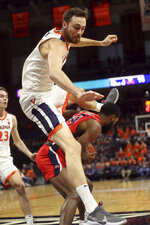 Virginia forward Jay Huff leaps over Stony Brook guard Andrew Garcia (23) during an NCAA college basketball game in Charlottesville, Va., Wednesday, Dec. 18, 2019. (AP Photo/Andrew Shurtleff)