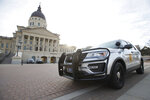 A Capitol Police vehicle with the Kansas Highway Patrol sits parked outside the Kansas Statehouse Thursday afternoon, Jan. 14, 2021, in Topeka, Kan. Governors in some states have called out the National Guard, declared states of emergency and closed their capitols over concerns about potentially violent protests. Though details remain murky, demonstrations are expected at state capitols beginning Sunday and leading up to President-elect Joe Biden's inauguration on Wednesday. (Evert Nelson/The Topeka Capital-Journal via AP)