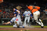 Los Angeles Dodgers' Will Smith (16) beats the tag by San Francisco Giants catcher Stephen Vogt (21) to score on a single by Enrique Hernandez during the eighth inning of a baseball game, Friday, Sept. 27, 2019, in San Francisco. (AP Photo/Tony Avelar)